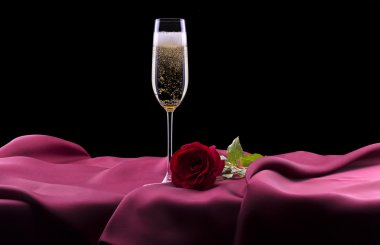 Glass of champagne and rose on black