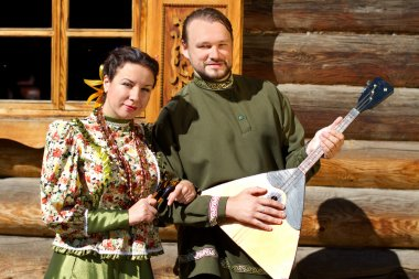 A girl and a young man with balalaika Cossack in national costumes against a wooden house
