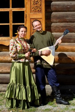 Slender boy with balalaika and beautiful Russian girl in national costume