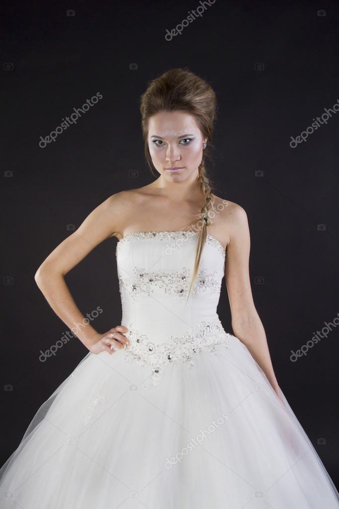 junge schöne Mädchen in einem Brautkleid auf dunklem Hintergrund ...