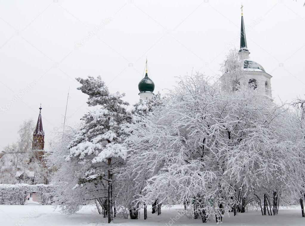 Winter alley in park and an Orthodox church spire