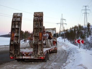 Tractor-trailer transports skidder