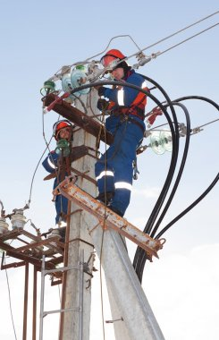 Electricians in blue overalls working at height