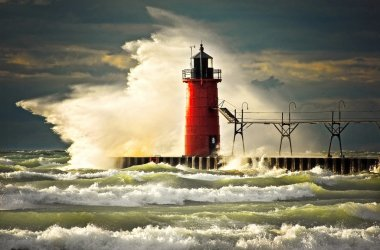 Wave slamming red lighthouse