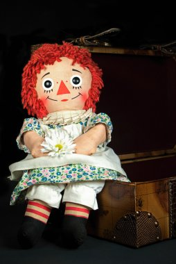 old rag doll on a suitcase