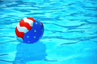 Patriotic beach ball in swimming pool