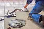 Photo Man laying tile flooring