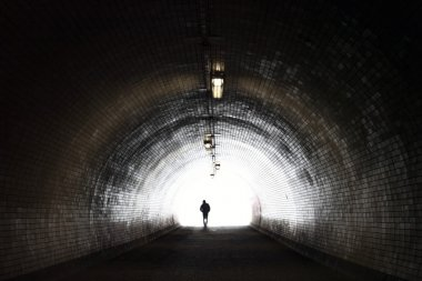 Human Silhouette in Light at The End of The Tunnel