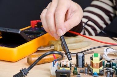 Women repairing circuit board with digital multimeter