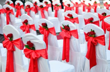 Wedding chairs decorated in white, ribbons and red rose.