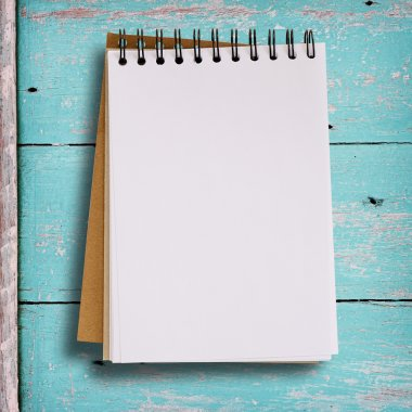 Open blank notebook on grunge wood background in green color.