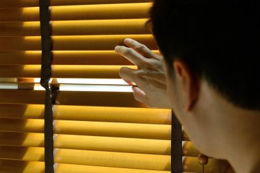 A man is looking out through the blinds