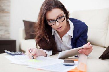 onun dijital tablet kullanarak evden çalışan genç bir kadın