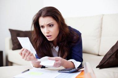 Desperate young woman looking at bills