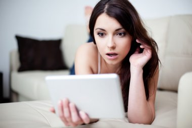 Surprised woman with tablet on couch