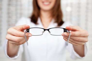 optometrist, optician giving glasses to try
