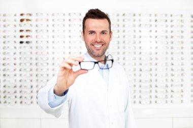 Happy optometrist, optician showing glasses