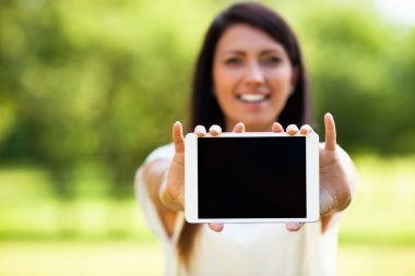 Woman showing tablet outdoors