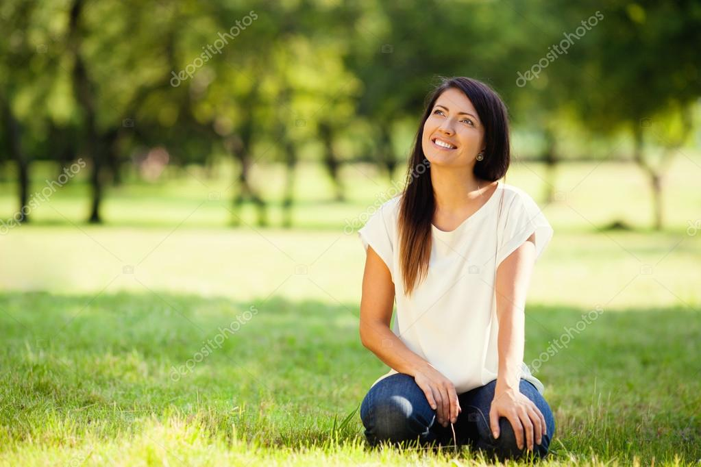 Beautiful woman sitting on grass in park