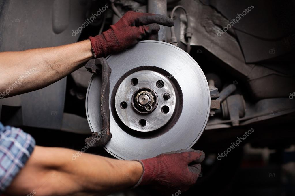 Car mechanic Repairing brakes on car