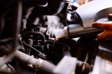 Car mechanic fills engine oil