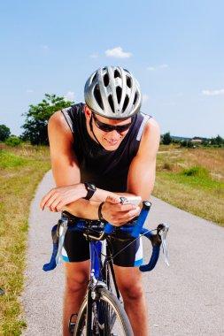 Triathlon cyclist texting on smartphone