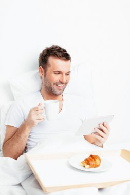 Man in bed with tablet and coffee