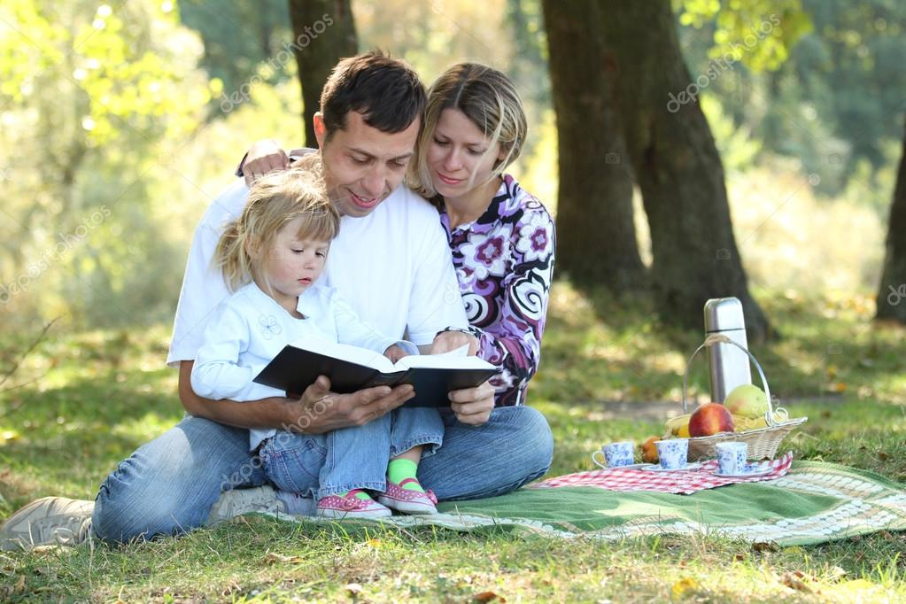 Young family with a child reading the Bible