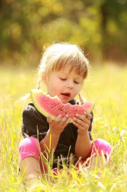 A beautiful little girl eating watermelon on nature