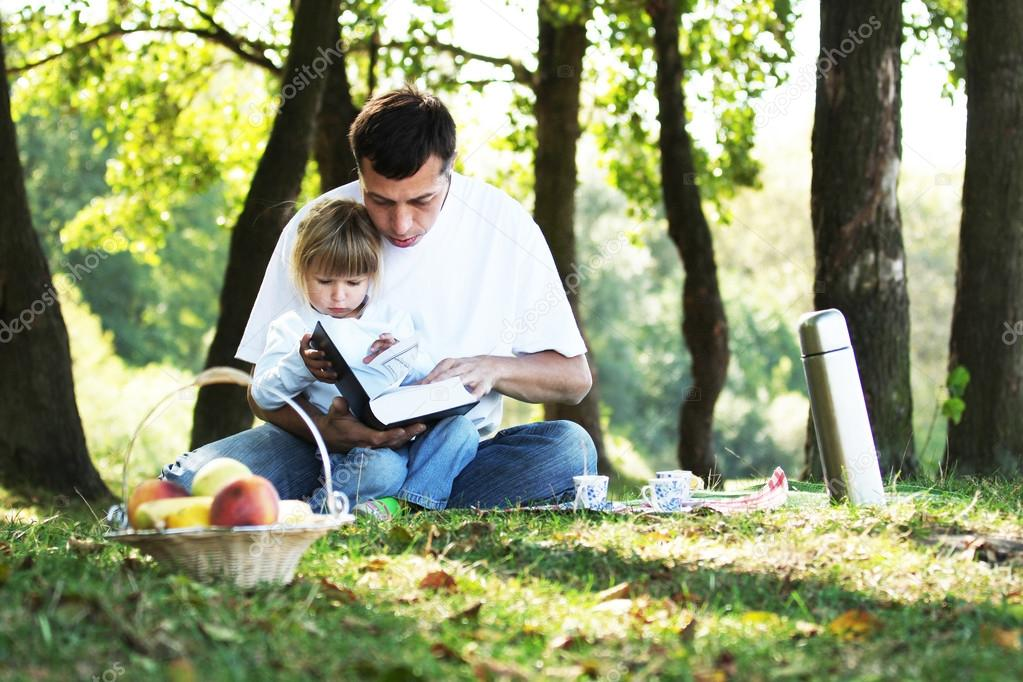 young father with a young daughter read the Bible in nature