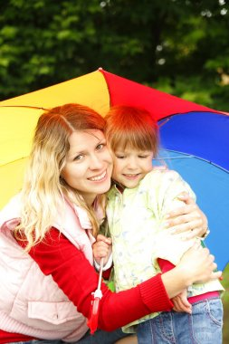 little girl with an umbrella in the rain with mom