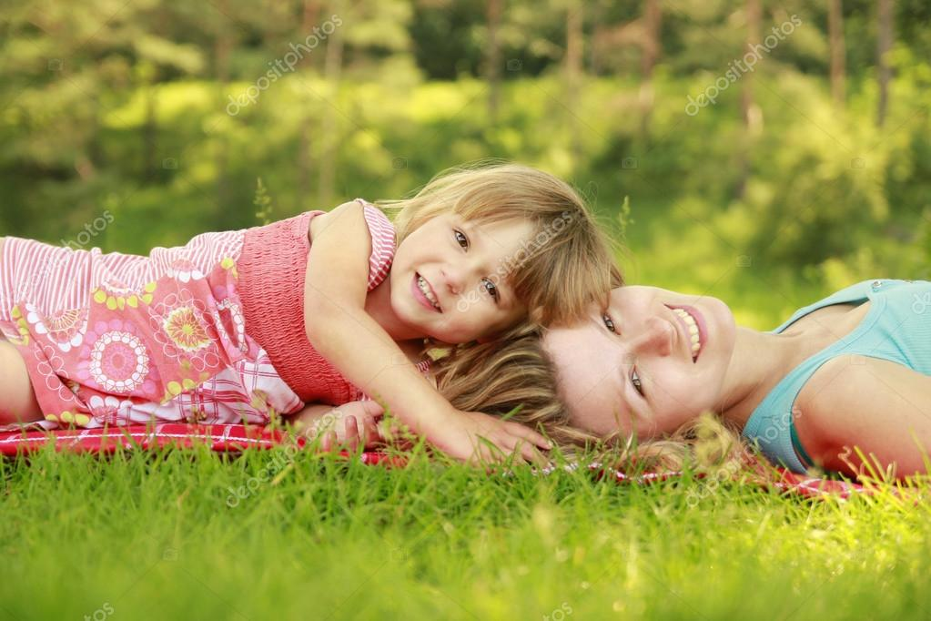 young mother and her little daughter playing on grass