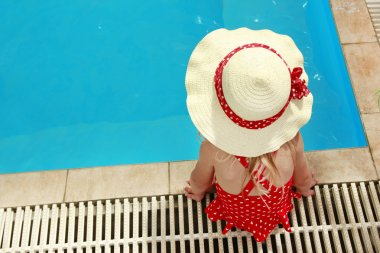 little girl in a hat floating in the pool
