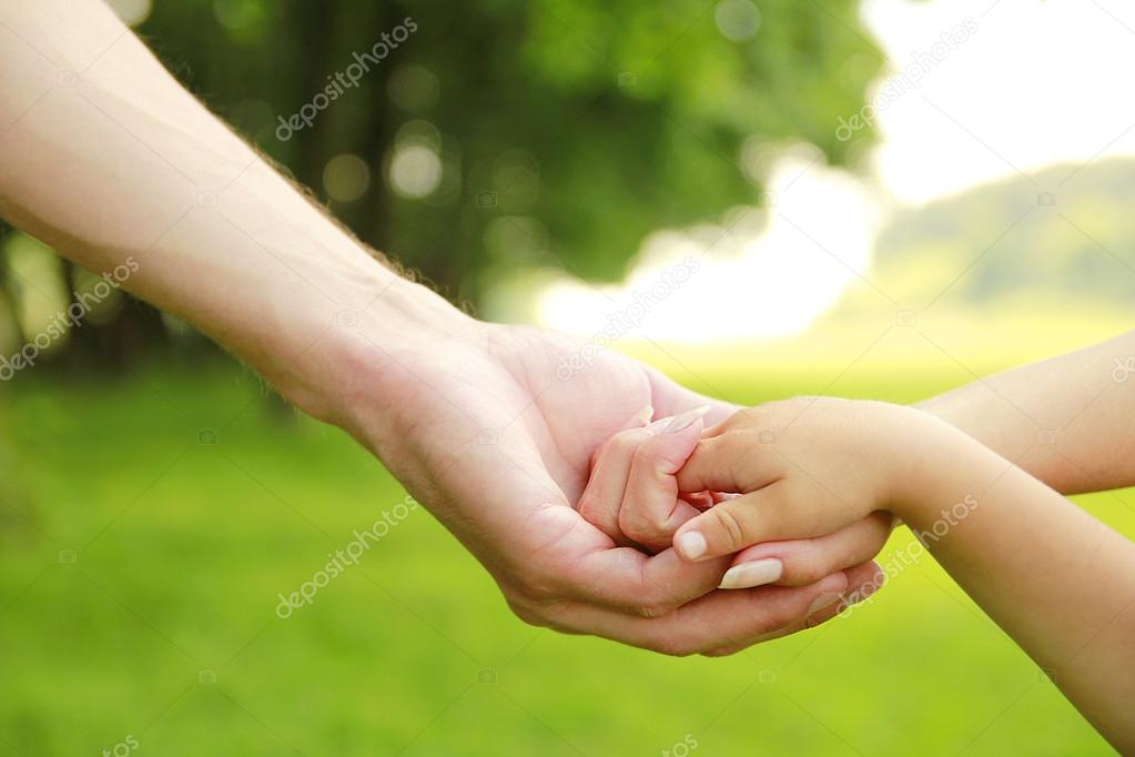 Parents hold the hand of  child