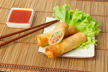 Fried spring rolls, one cut, on a plate