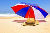 slaměný klobouk, sluneční brýle a slunečník na pláži