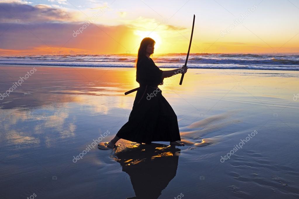 Young samurai women with Japanese sword(Katana) at sunset on the