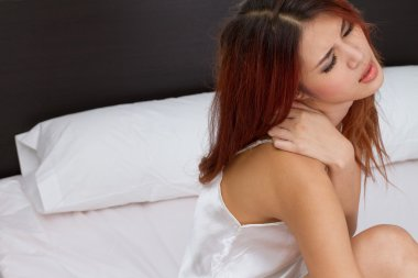 Woman on bed with neck or shoulder with negative feeling