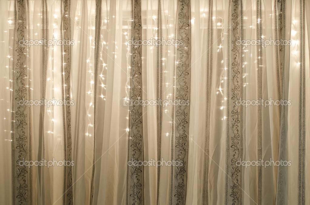 doorschijnende gordijnen versierd met elektrische garland foto van dmitrydesign