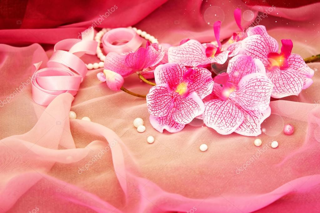 pink orchids, necklace, beads on a soft pink background