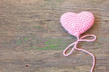 Pink knitted toy in the shape of heart on an old wooden background