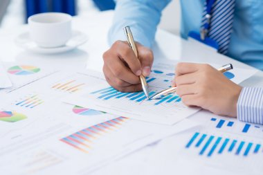 Cropped image of businesspeople analyzing financial graphs on the foreground stock vector