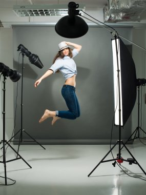 Portrait of a jumping model working in the professional photo studio stock vector