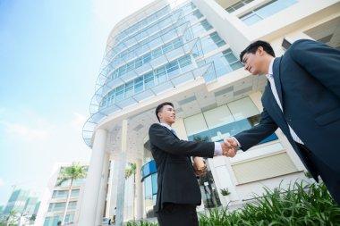 Asian businessmen shaking their hands