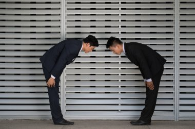 Business partners making a low bow