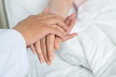 Doctor holding hand of the patient