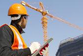 stavební dělník s jeřábem v pozadí