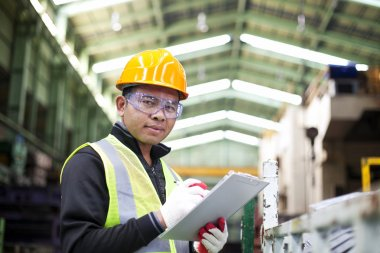 Factory worker with clipboard on the hand