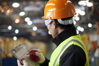Portrait of young engineer taking notes in the factory stock vector