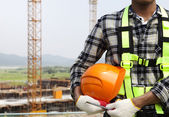 Close up construction worker holding helmet